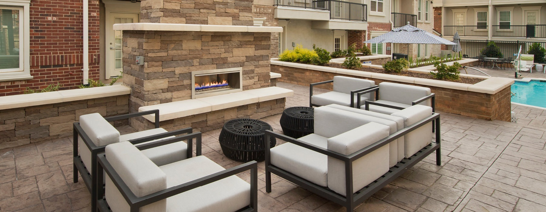 Outside living area with fireplace and four chair seating