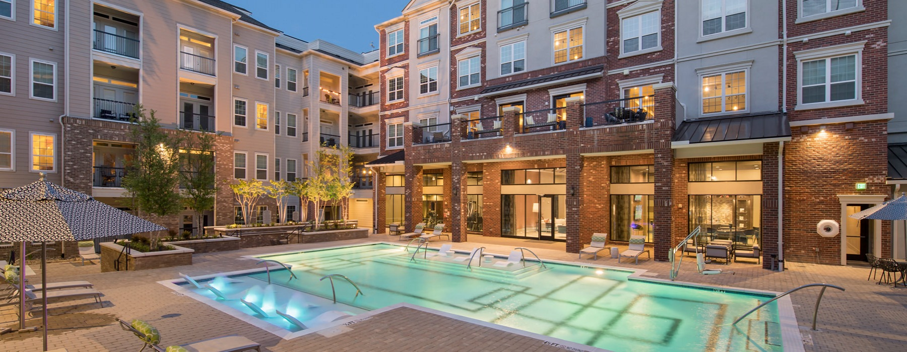 Creekside at Crabtree pool encompassed by gym, resident lounge, and apartment units